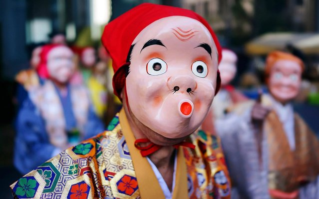 Artists wearing Japanese traditional clown masks stand for marching during the Konpira Festival at Kotohiragu shrine in Toranomon business district of Tokyo Friday, January 10, 2020. The shrine is dedicated to sailors and seafaring. (Photo by Eugene Hoshiko/AP Photo)