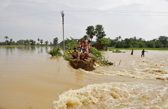 Flood-affected people sit on a broken embankment of a road damaged by the flood waters as they wait for relief supplies at Howrah district in West Bengal, India, August 5, 2015. (Photo by Rupak De Chowdhuri/Reuters)