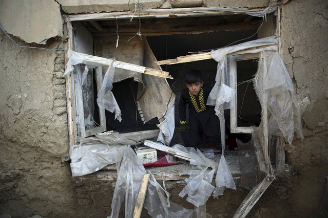 A boy inspects his damaged home after after an attack near the Bagram Air Base in Parwan province of Kabul, Afghanistan, Wednesday, December 11, 2019. A powerful suicide bombing Wednesday targeted an under-construction medical facility near the Bagram Air Base, the main American base north of the capital Kabul, the U.S. military said. (Photo by Rahmat Gul/AP Photo)