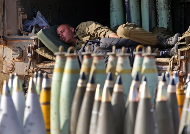 An Israeli soldier sleeps on a truck behind mobile artillery unit shells at a position on the Israel-Gaza border, July 11, 2014. Gaza rocket fire struck a gas station and set it ablaze in southern Israel, seriously wounding one person in the four-day-long offensive. (Photo by Lefteris Pitarakis/AP Photo)