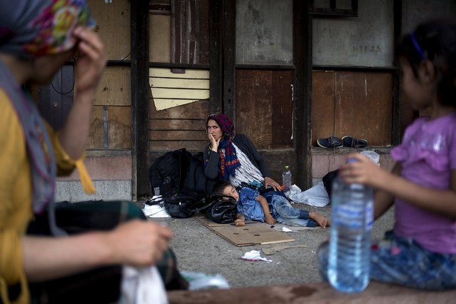 A migrant woman rests with her child as they wait for a train to arrive at Gevgelija train station in Macedonia, close to the border with Greece, August 14, 2015. (Photo by Stoyan Nenov/Reuters)