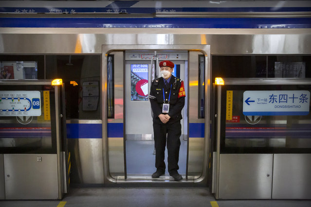 In this February 3, 2020, file photo, a security officer wearing a face mask stands on a subway train in Beijing. Health authorities are preparing for a possible pandemic as they work to contain a respiratory illness in China that's caused by a new virus. Governments are working to contain the virus by limiting travel, isolating sick people and keeping travelers returning from the affected region under quarantine to watch for symptoms. (Photo by Mark Schiefelbein/AP Photo/File)
