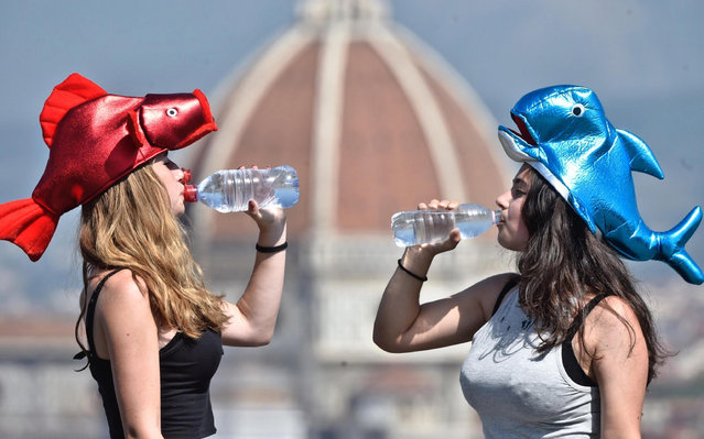 Two girls drink water with the background of Brunelleschi's dome of Florence cathedral during a heat wave in Florence, Italy, 01 August 2017. Temperatures are expected to reach 35-40 degrees Celsius (104F) during the day, according to weather reports. (Photo by Maurizio Degl'Innocenti/EPA)