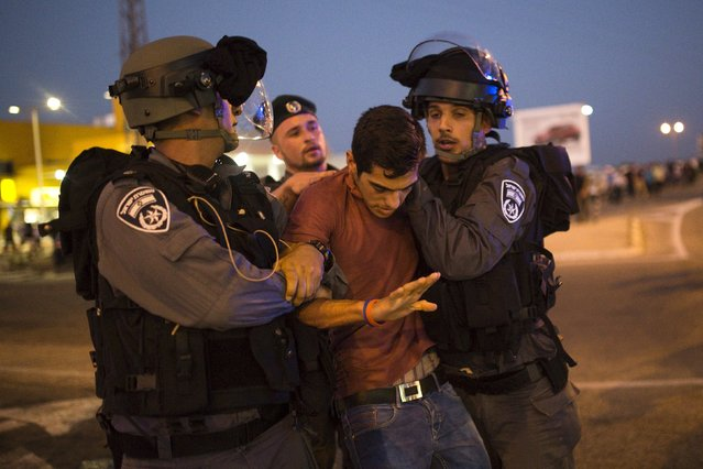 Israeli police officers detain a Palestinian activist during a protest in support of a hunger-striking Palestinian prisoner, Mohammed Allan, in the southern city of Ashkelon August 16, 2015. (Photo by Amir Cohen/Reuters)