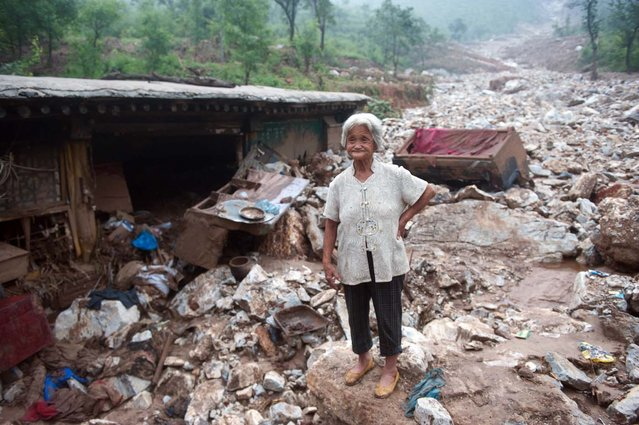 "An elderly woman stands by her damaged home in the devasted area in Beijing on July 26, 2012, after the worst rainstorms in six decades pounded the capital city on July 21 leaving the metropolis flooded and tens of thousands of people stranded in surging waters.  Authorities in Beijing said they would begin to ""strike"" out at online critics of the government response to recent record flooding, while declining again to release updated casualty tolls. (Photo by AFP)"
