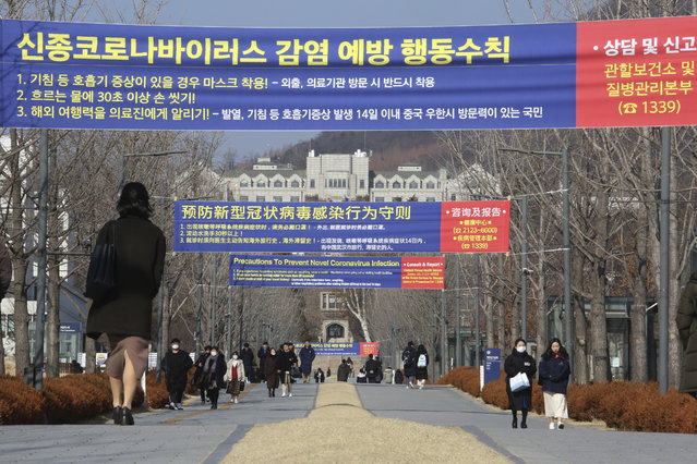 """People walk under banners about precautions against a new coronavirus at the Yeonsei University in Seoul, South Korea, Monday, February 10, 2020. China reported a rise in new virus cases on Monday, possibly denting optimism that its disease control measures like isolating major cities might be working, while Japan reported dozens of new cases aboard a quarantined cruise ship.The signs read: """"How to prevent a new coronavirus"""". (Photo by Ahn Young-joon/AP Photo)"""