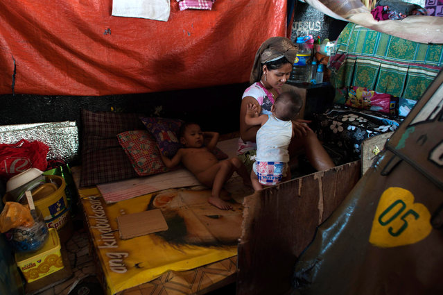 A family sit under a bridge, where they live on August 11, 2014 in Manila, Philippines. (Photo by Dondi Tawatao/Getty Images)