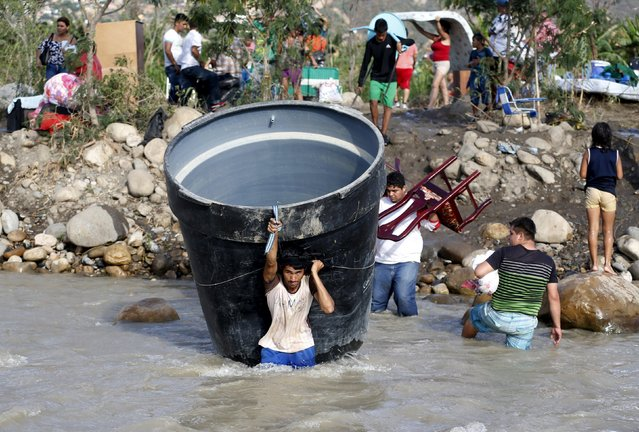 People carry their belongings while crossing the Tachira river border with Venezuela into Colombia, near Villa del Rosario village, August 25, 2015. The ongoing crisis on the border between Colombia and Venezuela should not be used for political point-scoring by leaders in either country ahead of elections in coming months, the Colombian government said on Tuesday. (Photo by Jose Miguel Gomez/Reuters)