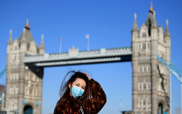 A member of the public poses for a photo in front of Tower Bridge whilst wearing a protective mask on March 22, 2020 in London, England. Coronavirus (COVID-19) has spread to at least 188 countries, claiming over 13,000 lives and infecting more than 300,000 people. There have now been 5,018 diagnosed cases in the UK and 233 deaths. (Photo by Alex Davidson/Getty Images)