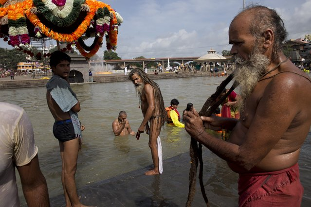 An Indian Sadhu, or Hindu holy man, right, dries his hair after a bath as others take a bath in the Godavari River during Kumbh Mela, or Pitcher Festival, in Nashik, India, Saturday,  August 29, 2015. (Photo by Tsering Topgyal/AP Photo)