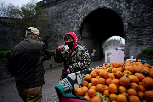 A street vendor wearing a face mask sells fruits in Jingzhou, after the lockdown was eased in Hubei province, the epicentre of China's coronavirus disease (COVID-19) outbreak, March 27, 2020. (Photo by Aly Song/Reuters)