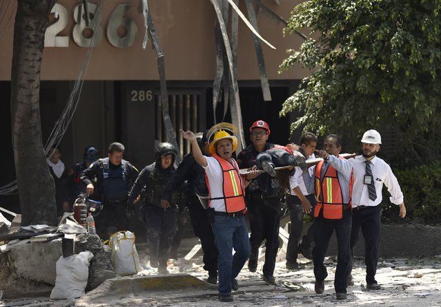 Rescuers carry an injured person on a stretcher in Mexico City on September 19, 2017. (Photo by Pedro Pardo/AFP Photo)