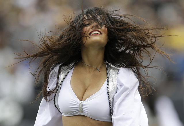 An Oakland Raiders cheerleader performs during the second half of an NFL football game against the Pittsburgh Steelers in Oakland, Calif., Sunday, October 27, 2013. (Photo by Marcio Jose Sanchez/AP Photo)