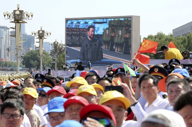 Spectators watch as a big electronic screen displays Chinese President Xi Jinping (back) inspecting the army at the beginning of the military parade marking the 70th anniversary of the end of World War Two, in Beijing, China, September 3, 2015. (Photo by Reuters/China Daily)