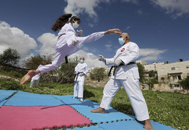 Beesan al-Jubeh, (L), Palestinian under-10 national karate champion, trains with her father Sami (R) and other family members, all wearing face masks and gloves due to the COVID-19 coronavirus pandemic, outside their house in the city of Hebron in the Occupied West Bank on April 9, 2020. (Photo by Hazem Bader/AFP Photo)