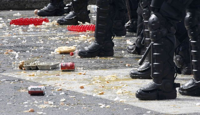 Eggs thrown by demonstrators are seen on the pavement as Belgian riot police officers stand guard as farmers and dairy farmers from all over Europe take part in a demonstration outside an European Union farm ministers emergency meeting at the EU Council headquarters in Brussels, Belgium, September 7, 2015. (Photo by Jacky Naegelen/Reuters)
