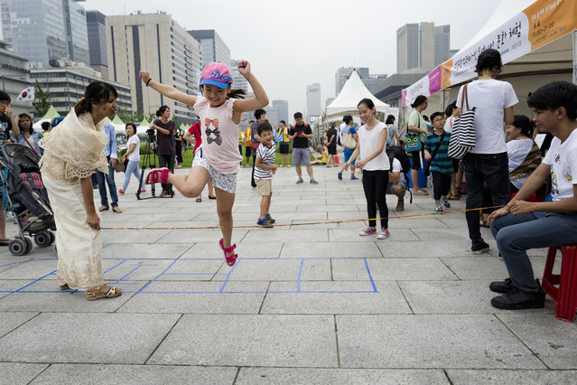 Kids plays Philippine traditional game with a elastic string at a temporal cultural experience zone on Gwanghwamun Square on July 29, 2015 in Seoul, South Korea. (Photo by Shin Woong-jae/The Washington Post)