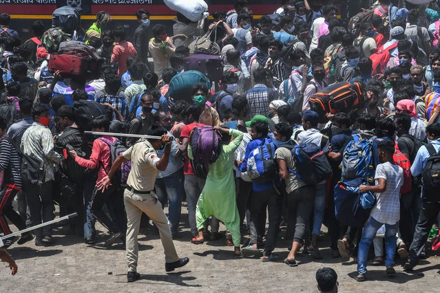 A policeman disperses migrant workers gathered outside a railway station intending to board a special service train without valid tickets to return back to their home towns during a nationwide lockdown imposed as a preventive measure against the COVID-19 coronavirus, in Mumbai on May 19, 2020. (Photo by Indranil Mukherjee/AFP Photo)
