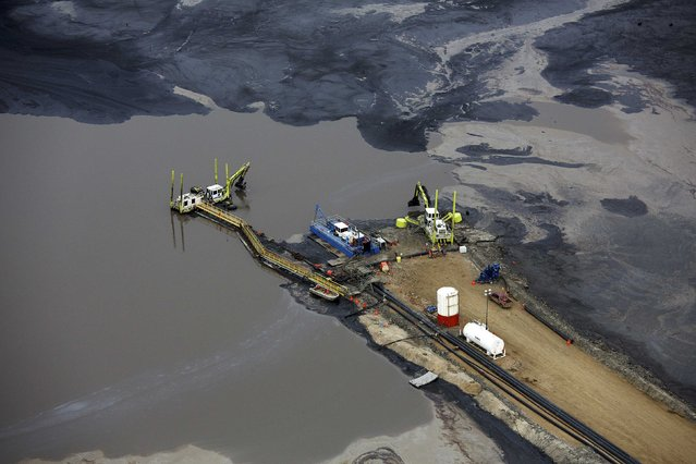 Heavy equipment works on a tailings pond at the Suncor tar sands operations near Fort McMurray, Alberta, September 17, 2014. (Photo by Todd Korol/Reuters)