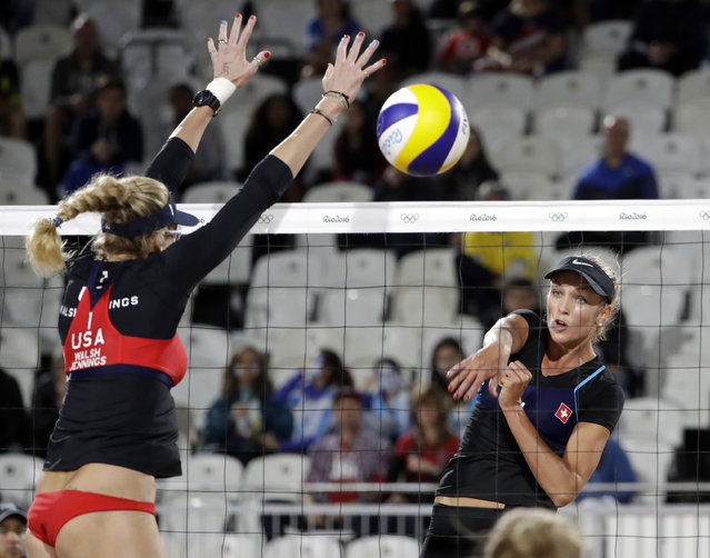 Switzerland's Anouke Verge-Depre, right, spikes past United States' Kerri Walsh Jennings during a women's beach volleyball match at the 2016 Summer Olympics in Rio de Janeiro, Brazil, Wednesday, August 10, 2016. (Photo by Marcio Jose Sanchez/AP Photo)