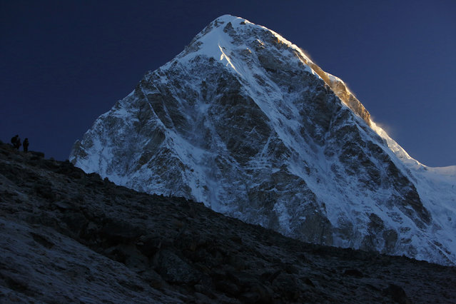 Light from a sunrise illuminates Mount Pumori, which is approximately 23294 high, as trekkers look at the mountains from Kala Patthar in Solukhumbu District May 7, 2014. (Photo by Navesh Chitrakar/Reuters)