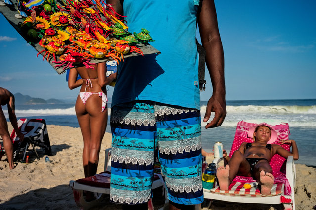 """Copacabana Beach, Rio de Janeiro. """"Beach sellers are everywhere, all the time, in Rio. Yet this guy with his patterned shorts matching the sea and sky behind, gave me just what I needed to photograph the women nearby. A bikini shot all by itself just doesn't work. There are lots of bikinis in Rio, and yet I have very few photos to depict this in a way that is not a bikini shot for its own sake"""". (Photo by David Alan Harvey/The Guardian)"""