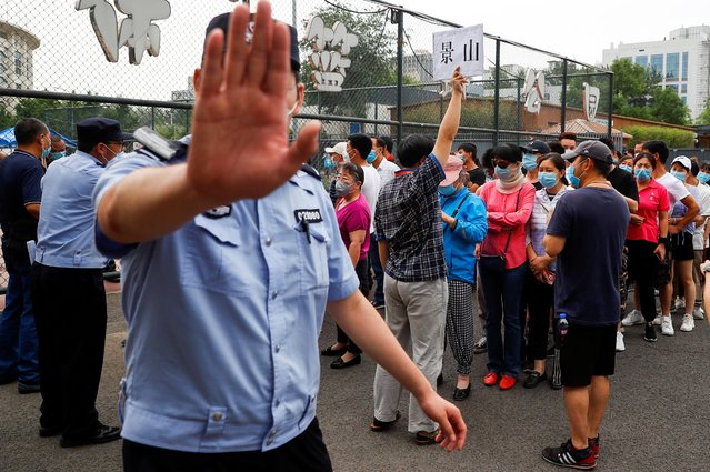 A police officer gestures at a photographer as people line up to get a nucleic acid test at a sport center after a spike of cases of the coronavirus disease (COVID-19), in Beijing, China on June 17, 2020. (Photo by Thomas Peter/Reuters)