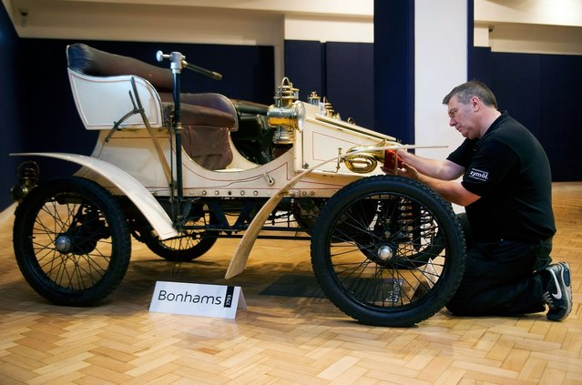 Bonhams employee Craig Binns polishes a, 1903 two seater moter car, the world oldest surviving Vauxhall, on November 1, 2012 in London, England. The Car is part of a Veteran Car Sale at Bonhams and is valued at around 80,000 pounds  (Photo by Bethany Clarke)