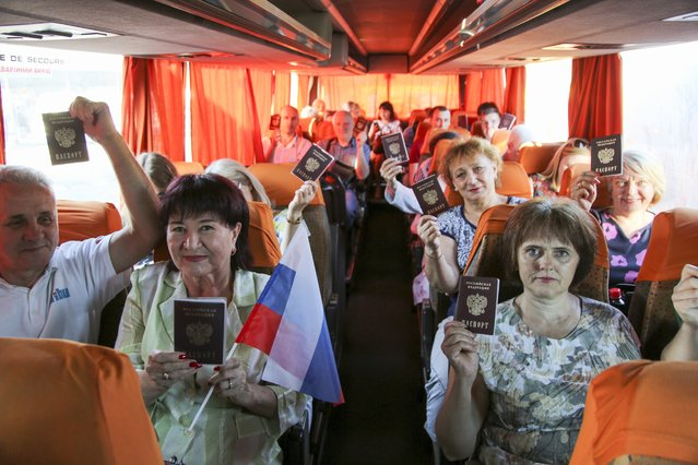 In this photo taken on Saturday, June 27, 2020, people show their Russian passports sitting on a bus to Russia at a bus to Russia at a bus stop in Donetsk, eastern Ukraine. Residents of separatist-controlled regions in eastern Ukraine who have Russian citizenship are traveling to Russia to vote on constitutional amendments that would allow President Vladimir Putin to remain in power until 2036. Authorities of the self-proclaimed Luhansk and Donetsk People's Republics have organized bus services to polling stations in the neighboring Rostov region in Russia, in what is seen by many as part of the wide-spread effort to boost turnout at the controversial plebiscite. (Photo by Alexei Alexandrov/AP Photo)