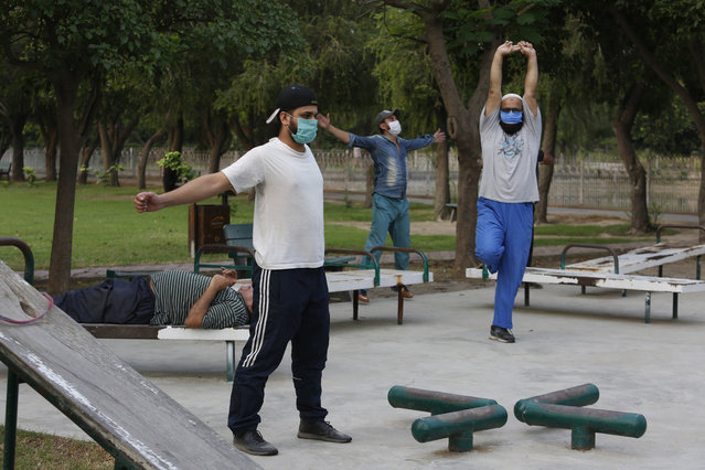 People exercise in a park in Lahore, Pakistan, Friday, June 5, 2020. Government of Pakistan's Punjab province has reopened parks in different cities of the province including Lahore amid coronavirus outbreak. (Photo by K.M. Chaudary/AP Photo)
