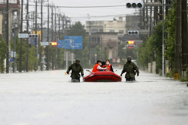 Japan Self Defense Force members rescue residents on a rubber boat on a flooded road hit by heavy rain in Omuta, Fukuoka prefecture, southern Japan Tuesday, July 7, 2020. (Photo by Juntaro Yokoyama/Kyodo News via AP Photo