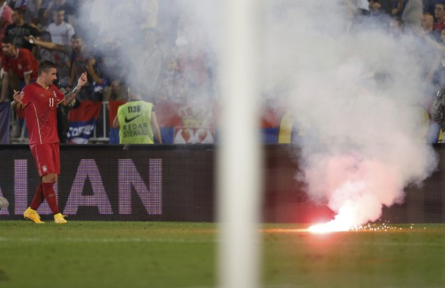Aleksandar Kolarov of Serbia reacts as flares are thrown to the pitch during their Euro 2016 Group I qualifying soccer match against Albania at the FK Partizan stadium in Belgrade October 14, 2014. (Photo by Marko Djurica/Reuters)