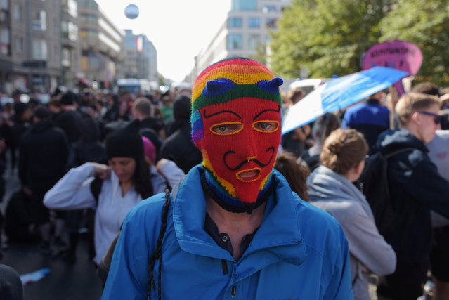 A Blockupy demonstrator wears a mask during a protest in front of the German labour ministry in Berlin, Germany September 2, 2016. (Photo by Stefanie Loos/Reuters)