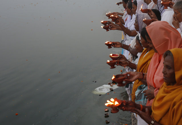 Widows, who have been abandoned by their families, hold earthen oil lamps as they offer prayers on the banks of the river Yamuna as part of Diwali celebrations organised by non-governmental organisation Sulabh International in Vrindavan, Uttar Pradesh October 21, 2014. (Photo by Ahmad Masood/Reuters)