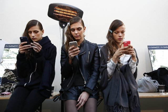 Models look at their mobile phones backstage before the Guy Laroche Spring/Summer 2016 women's ready-to-wear fashion show during Paris fashion Week, France, September 30, 2015. (Photo by Benoit Tessier/Reuters)
