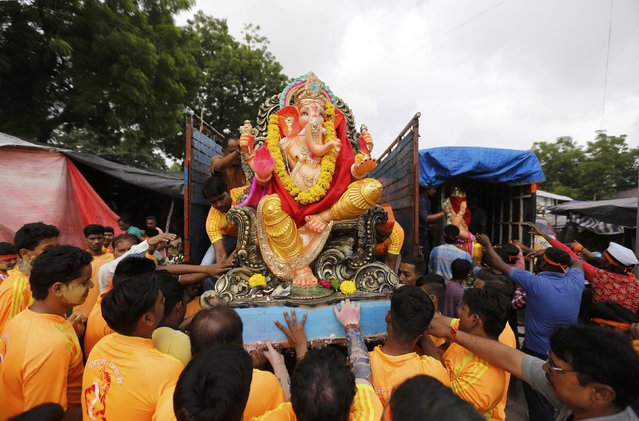 An idol of the Hindu god Ganesh, the deity of prosperity, is loaded unto a supply truck on the first day of the Ganesh Chaturthi festival in Ahmedabad, India, September 5, 2016. (Photo by Amit Dave/Reuters)