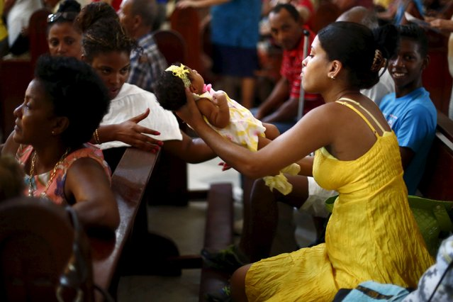 A parishioner holds a baby during a mass celebrating Pope Francis' visit, in the church of the Virgin of Charity of El Cobre in Havana, September 18, 2015. (Photo by Edgard Garrido/Reuters)