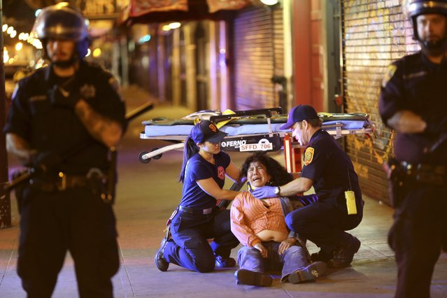 A woman is assisted by medical personnel during a celebration in the Mission District in San Francisco, California October 29, 2014. The San Francisco Giants beat the Kansas City Royals 3-2 on Wednesday to win their third World Series title in five seasons. (Photo by Robert Galbraith/Reuters)