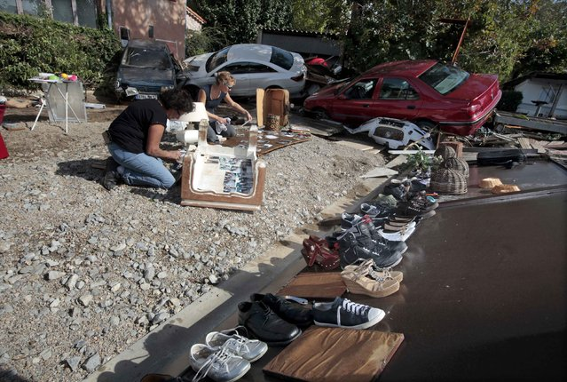 Women place family pictures out to dry, saved from their home, near cars that were damaged after flooding caused by torrential rain in Biot, France, October 4, 2015. (Photo by Eric Gaillard/Reuters)