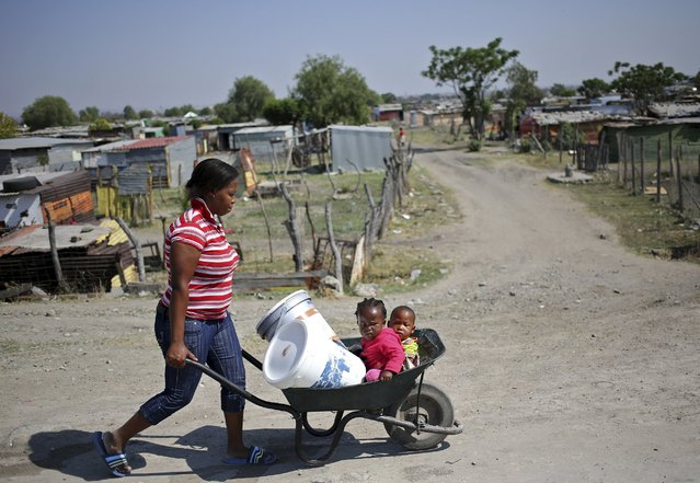 A women pushes a wheel barrow transporting water and her children at Siza informal settlement near Anglo American Platinum's Thembelani mine in the mining town of Rustenburg, northwest of Johannesburg, October 5, 2015. (Photo by Siphiwe Sibeko/Reuters)