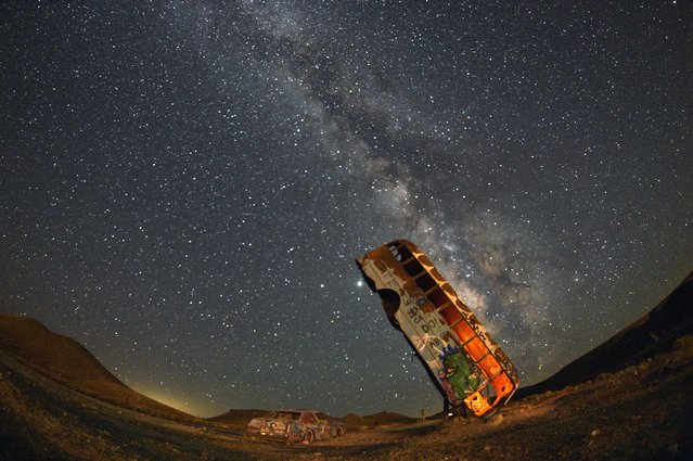 The Milky Way galaxy is seen in the sky above the International Car Forest of the Last Church in Goldfield, Nevada on July 18, 2020. The roadside attraction, created in 2002 by Mark Rippie, has over 36 automobiles including cars, trucks, vans and buses that have been balanced on their ends or stacked on top one of another. (Photo by David Becker/AFP Photo)