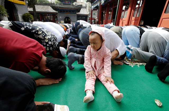 A child sits among people attending prayers for Eid al-Adha festival at Niujie mosque in Beijing, China September 12, 2016. (Photo by Jason Lee/Reuters)