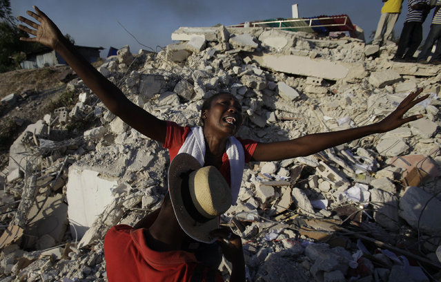 Maxi Phalone sings praises to God after her sister was pulled alive from the rubble of a collapsed building in Port-au-Prince, Monday, January 18, 2010. (Photo by Julie Jacobson/AP Photo)