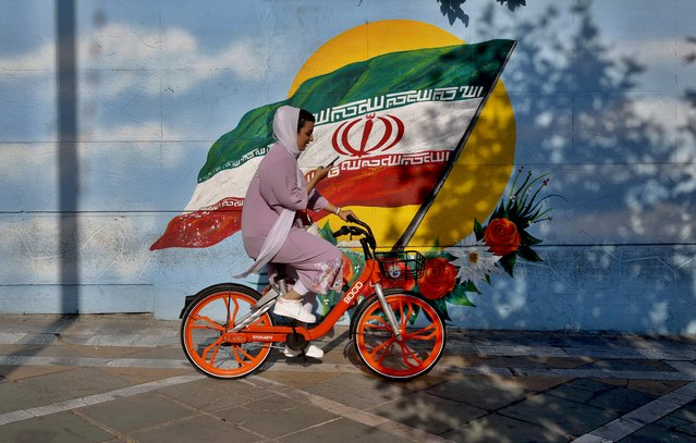 An Iranian woman rides a bicycle next to a mural of Iran's national flag in Tehran, Iran, 28 July 2020. According to figures released by the Iranian Health Ministry, Iran hits a new record of daily death toll since the coronavirus crisis started, announcing 235 deaths from coronavirus disease and more than 2,500 new cases diagnosed within a 24-hour period. (Photo by Abedin Taherkenareh/EPA/EFE)