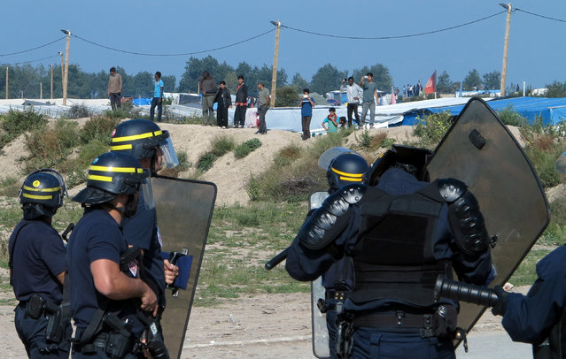 "French riot policemen stand guard at the entrance to the ""Jungle"" as dozens of migrants try to storm lorries which are heading towards the ferry terminal in Calais, France, September 21, 2016. (Photo by Pascal Rossignol/Reuters)"