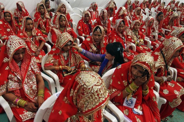An Indian volunteer, center, adjusts the costume of a bride during a mass marriage of 162 Muslim couples in Ahmadabad, India, Sunday, March 3, 2013. Mass marriages in India are organized by social organizations primarily to help the economically backward families who cannot afford the high ceremony costs as well as the customary dowry and expensive gifts that are still prevalent in many communities. (Photo by Ajit Solanki/AP Photo/LaPresse)