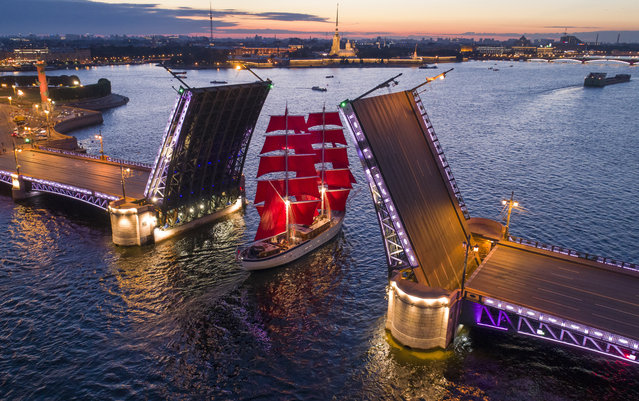 A brig with scarlet sails travels through the Dvortsovy (Palace) drawbridge rising above the Neva River during a rehearsal for the the Scarlet Sails festivities marking school graduation which will take place on June 24 in St. Petersburg, Russia, early Monday, June 17, 2019. (Photo by Dmitri Lovetsky/AP Photo)