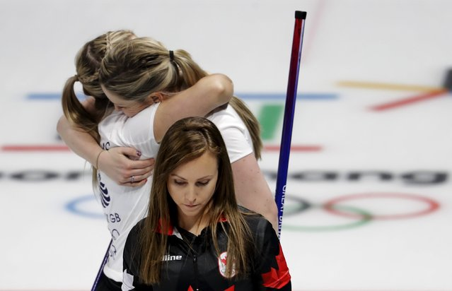 Canada's skip Rachel Homan, center, leaves the ice as Britain's Lauren Gray, right above, and Vicki Adams embrace celebrating winning a women's curling match at the 2018 Winter Olympics in Gangneung, South Korea, Wednesday, February 21, 2018. (Photo by Natacha Pisarenko/AP Photo)