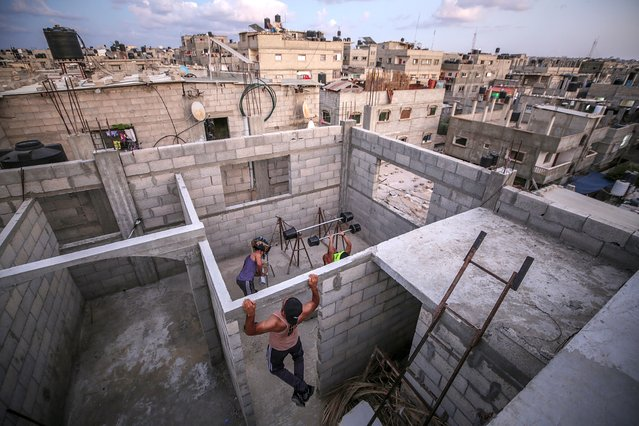Palestinian bodybuilders work out on the rooftop of a house amid the ongoing coronavirus pandemic, in Rafah, southern Gaza strip, 04 October 2020 (issued 05 October 2020). The Gaza Strip has been under an emergency COVID-19 lockdown since 25 August 2020. (Photo by Mohammed Saber/EPA/EFE)