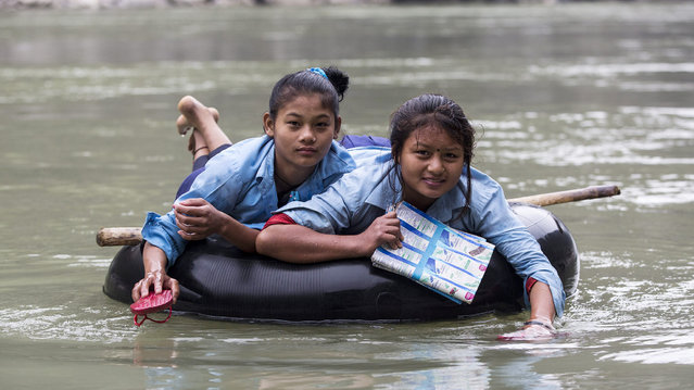 Two fourteen-year-old Nepalese students use their sandals to paddle across the Trishuli river on their way to school in Dhading District, some 90 kilometers from capital Kathmandu, Nepal, 04 December 2014. The two girls  cross the river everyday on an inflatable rubber tube because the local authorities have failed to build a promised bridge. (Photo by Narendra Shrestha/EPA)